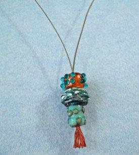 Marlein Bong, glazen hanger in blauwe tinten aan staalkabel, gedeeltelijk verkoperd.