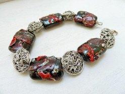 """Nicoline Lenskens, """"Ratana"""", armband met zwarte kralen bewerkt met rode 'shards' ook handgemaakt en Thaise zilveren draadkralen."""