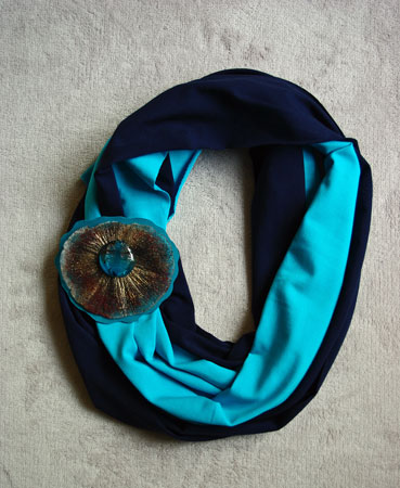 Monica Ligteringen, Bicolore tricot sjaal: blauw/turkoois. Broche: epoxy gietsel met pyrietzon met glas en turkoois leer, ook afzonderlijk te dragen.