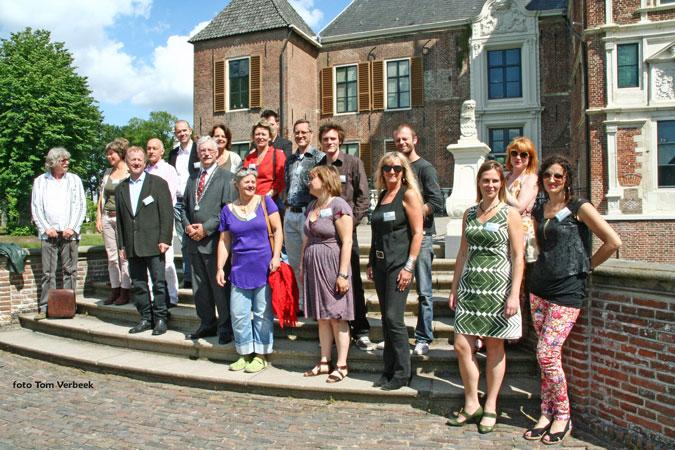 Burgemeester Hans van der Hoeve met de deelnemende kunstenaars op het bordes van kasteel Cannenburch.