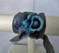 Gabriëlle Bolt, Armband met blauwe sculptuur op draad, met suede-band om pols gewikkeld. Er is een bijpassend collier.