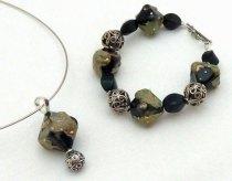 """Nicoline Lenskens, set """"Elyssa"""", hanger en armband, zwarte glaskralen gedecoreerd met handgeblazen 'glasscherven', micapoeder en fijn-zilverdraad."""