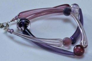 Monique Zwinkels, Collier lang model, ketting van diverse paarse kralen, geblazen en gemaakt aan de mandrel, sterling zilveren sluiting.