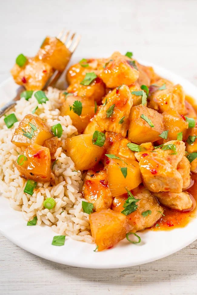 Slow Cooker Hawaiian Chicken with Pineapple atop bed of white rice on plate with fork