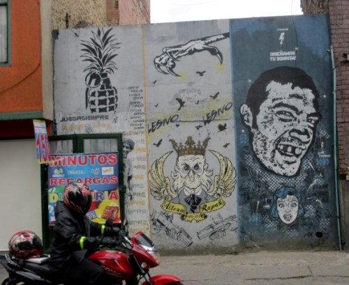 In this collaboration of graffiti artists, the middle character (by Lesivo) likely depicts ex-president Uribe or Christopher Colombus as a hawklike king surrounded by guns. To the left is a pineapple grenade by DJ Lu, and to the right is a depiction by Toxicomano of the effects of 'bazooka'. This cheap Colombian crack has such strength that one's teeth falls out. Above the head reads 'We design your smile'.