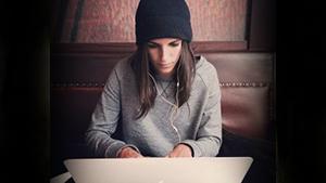femme avec des écouteurs sur un ordinateur portable
