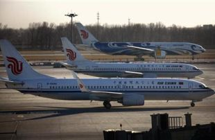 Air China planes pass each other on tarmac and runway at Beijing International Airport
