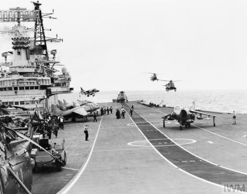 THE FALKLANDS CONFLICT, APRIL - JUNE 1982 (FKD 128) Flight deck operations on board HMS HERMES during her preparations for the Falklands Conflict. A British Aerospace Sea Harrier FRS.1 of 800 Naval Air Squadron lands on the starboard quarter while two Westland Sea Kings hover off the port quarter in preperation for a landing. Note the white underside of the Sea Harrier indicating this image was taken during the journey south towards the conflict zo... Copyright: © IWM. Original Source: http://www.iwm.org.uk/collections/item/object/205190438
