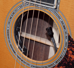 The built-in pickup system on this acoustic guitar allows the performer to blend two different pickup sources that are sent to a single output jack which gets connected to a direct box and the PA.