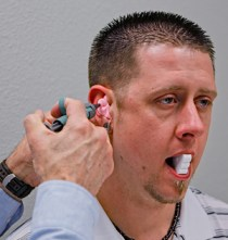 An audiologist taking an ear impression that will be used to make custom-molded in-ears.