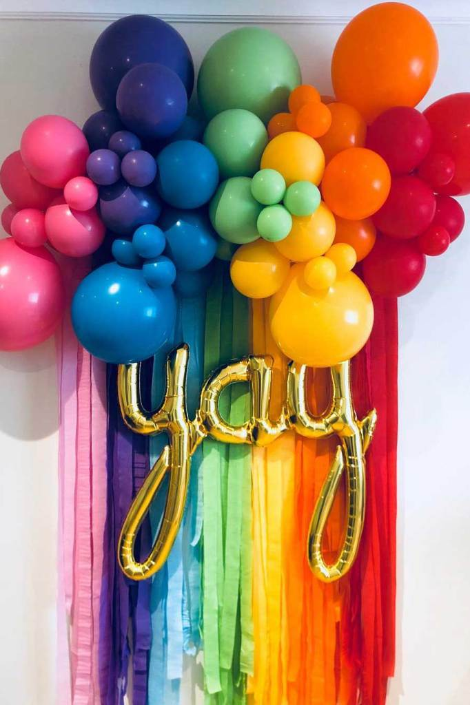 Backdrop idea for party with yay balloon against rainbow and clouds