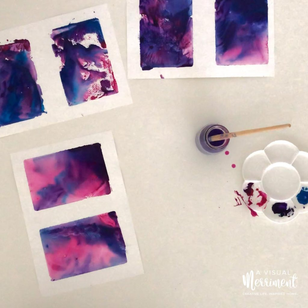finished easy watercolour paintings with messy paint tray and brush in water