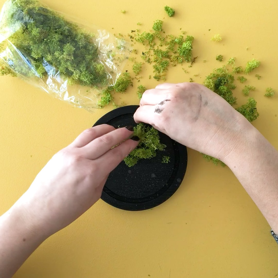 Begin attaching artificial moss to base once glue is tacky