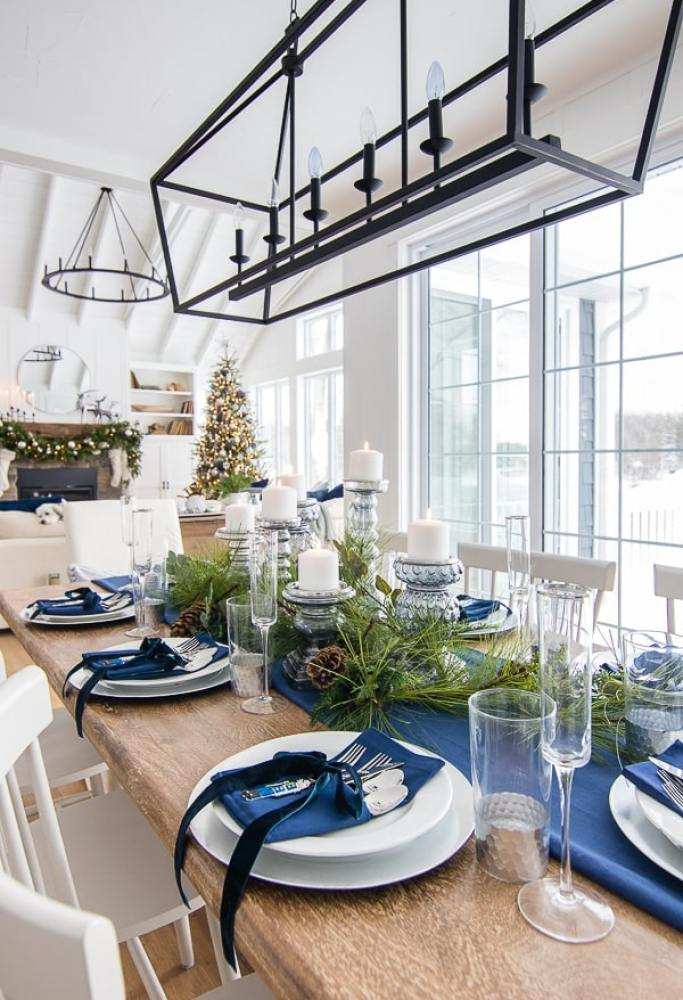 navy blue and silver christmas table setting with ribbons and greenery