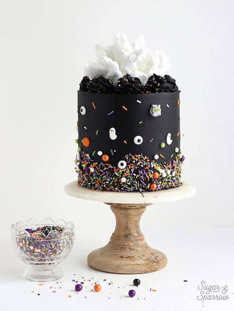 black halloween cake on stand decorated with colourful sprinkles