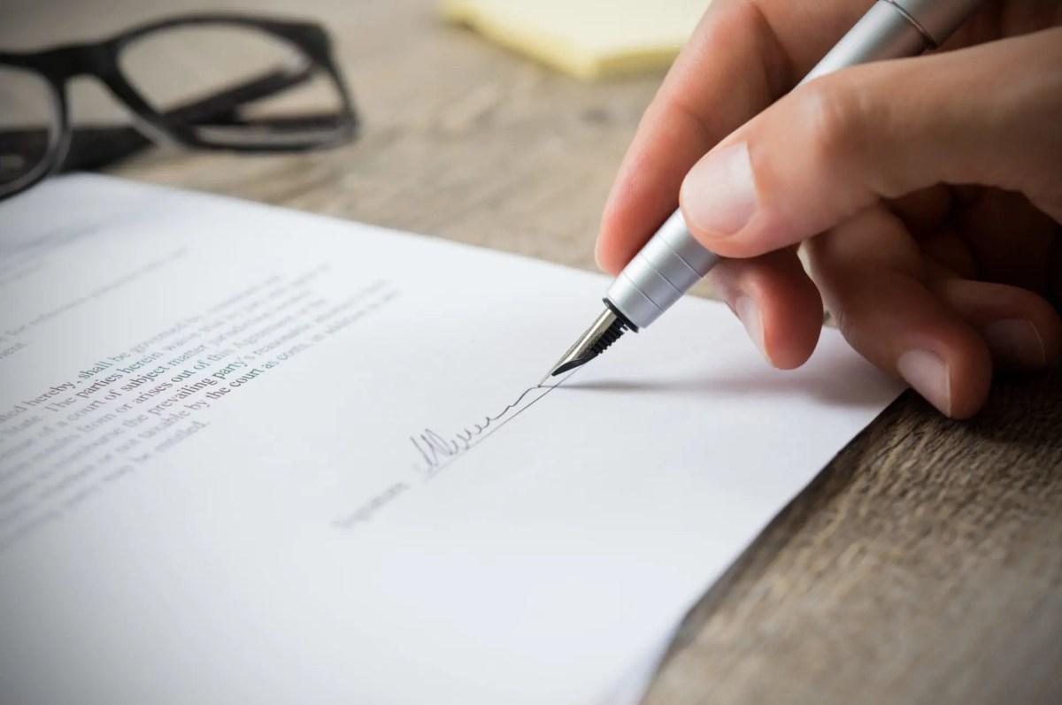 man signing contract PM2TY9P - Domaines d'expertises | Droit International et Européenne des Droits de l'Homme