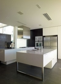 Minimalistic white kitchen with a dining area  by Elmar ...