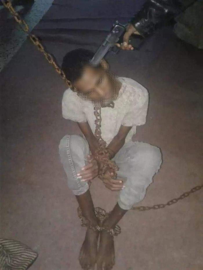 Un giovane eritreo minacciato con la pistola da un trafficante di esseri umani dopo esser stato ridotto in catene. Queste immagini vengono inviate dagli schiavisti ai parenti dei detenuti nel lager di Bani Walid per ricattarli Le pubblichiamo per documentare l'orrore che si consuma in quei campi libici