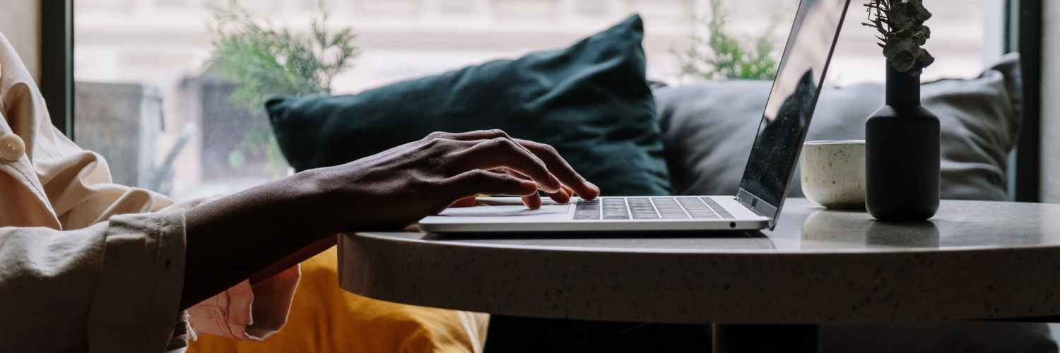 person in red pants sitting on couch using macbook