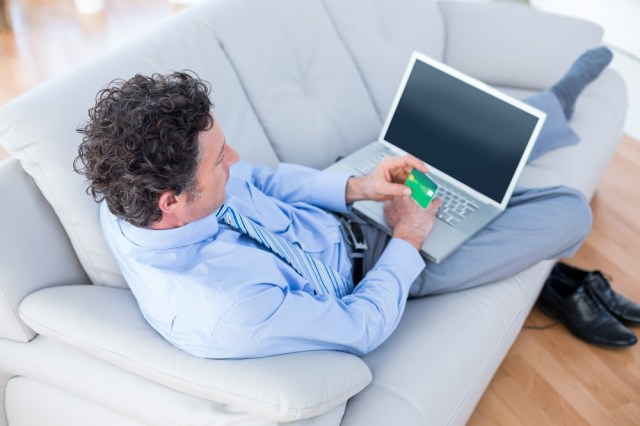Businessman doing online shopping on couch in living room.jpeg