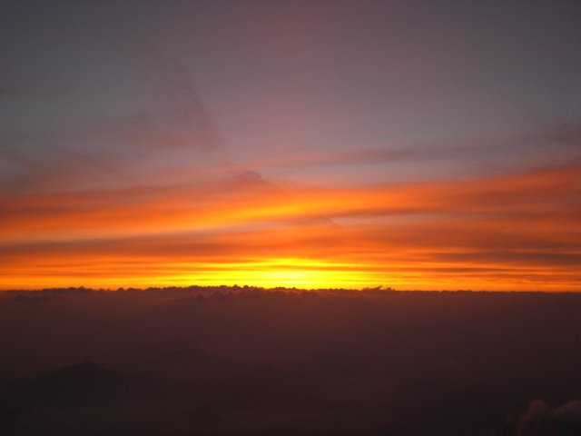 The sun rising above the clouds