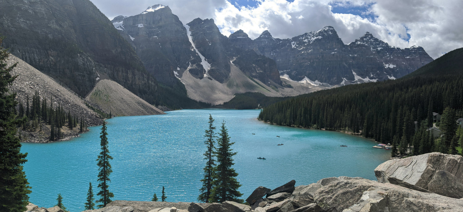 Moraine Lake's bright blue waters below towering peaks