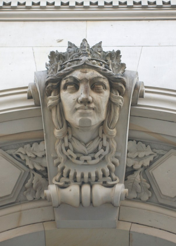 Architectural detail of classical head over entry of building from early 1900s