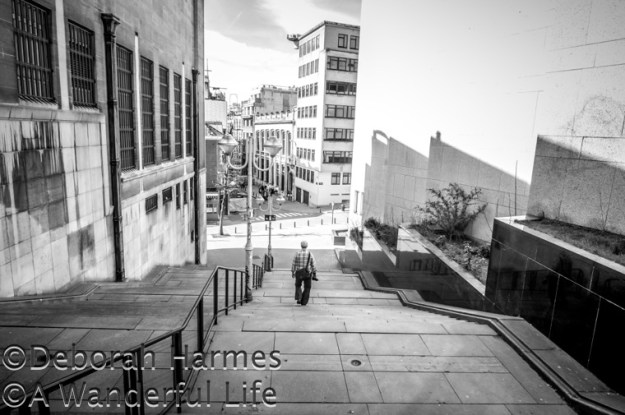 Man walks down exterior stairs in deep shade on a sunny day in Brussels, Belgium. B&W