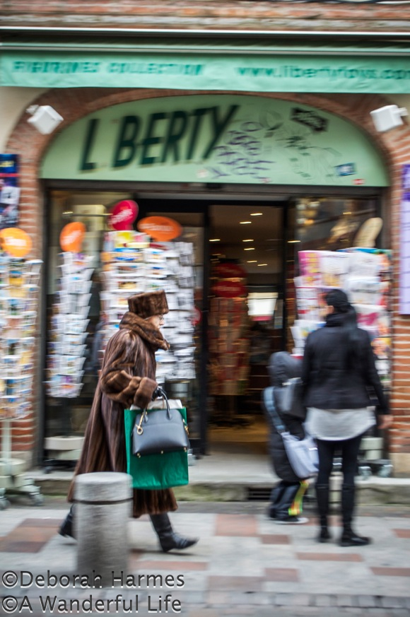 Clad in a full fur coat and fur hat, a woman bustles through the shopping district on Rue du Taur in Toulouse, France.