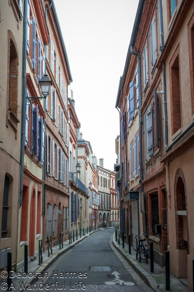 A slight curve in a narrow road filled with soft pink-coloured brick buildings in Toulouse, France.