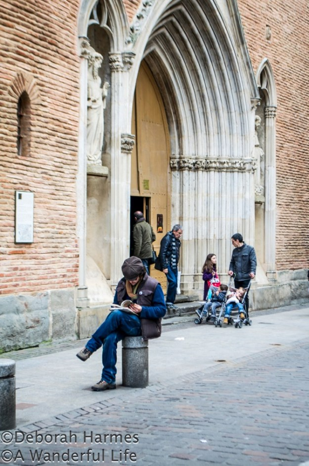 Man sitting on a bollard in front of the Notre Dame du Taur church entry reading a guidebook.