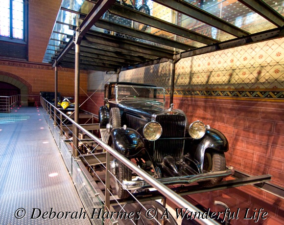 Vintage cars on suspended racks high above the floor below.