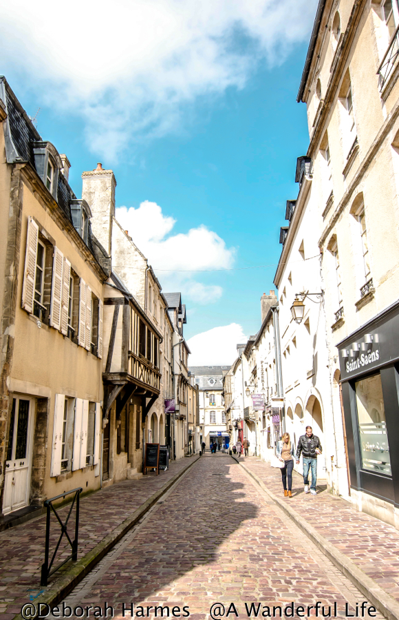 People walking down a small cobbled street in the shopping district of Bayeux in Normandy, France on a bright and sunny day.