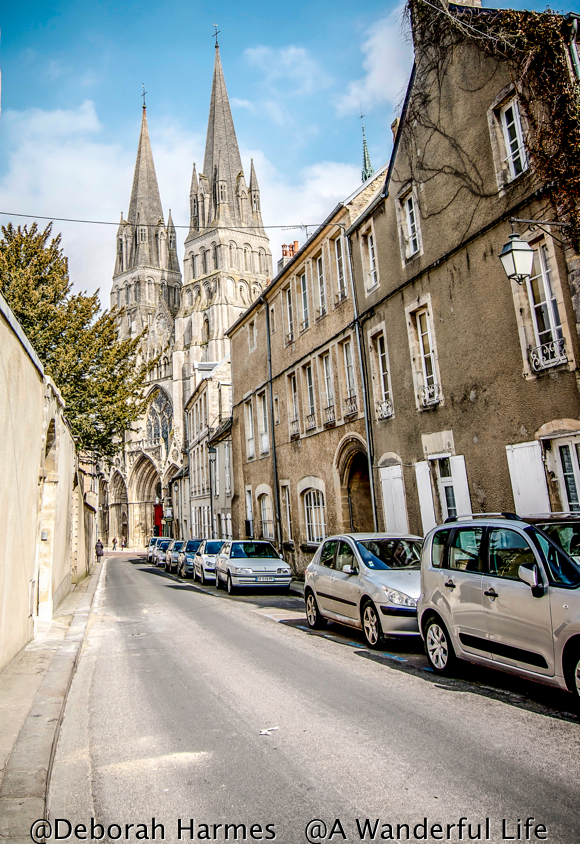 Looking down a narrow one way street in Bayeux, Normandy, France towards the 11th Century medieval cathedral at the end of the block.