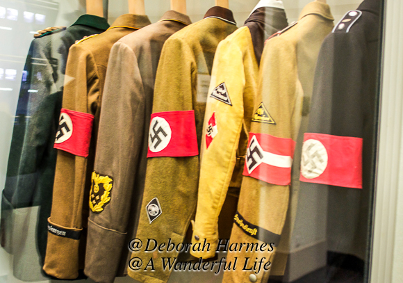 Row of German uniform jackets with a swastika on each of them.