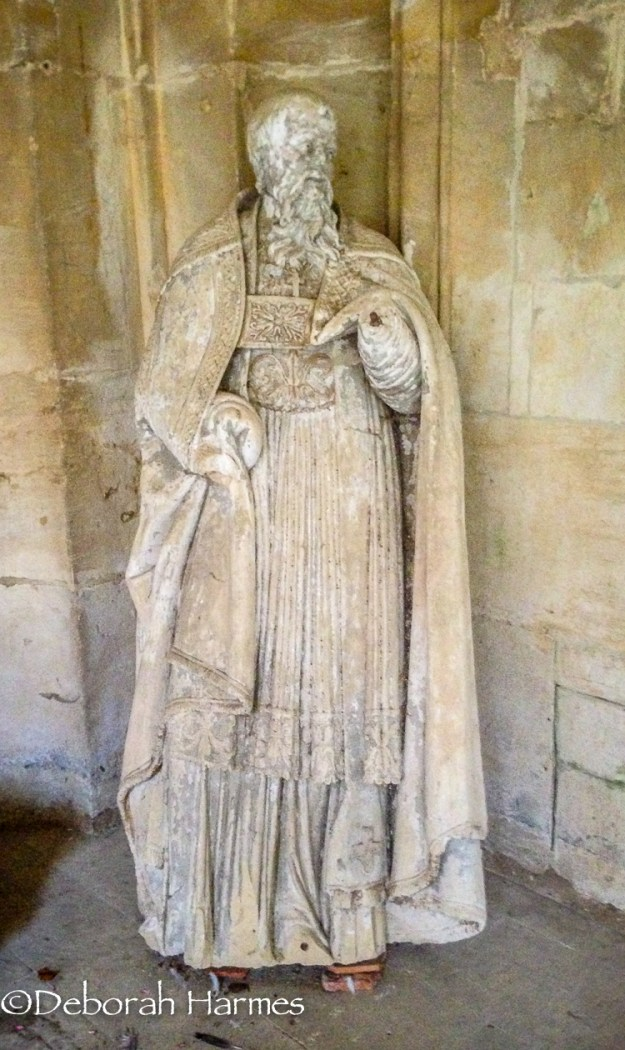 Leaning against a wall of the cloister, a statue awaits restoration of the abbey in Saint-Pierre-sur-Dives.