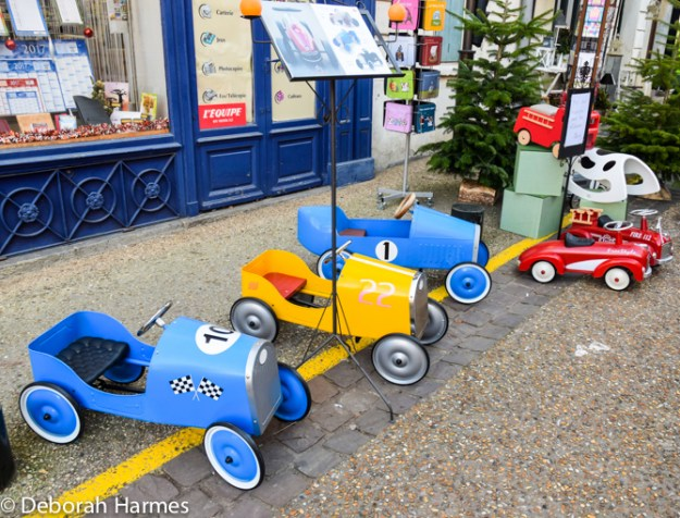Toddler sized toy cars outside shop in Normandy, France.