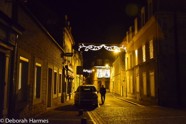 A man walks down a darkened street in northern France in mid-winter.