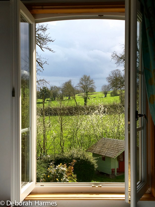 View of the Normandy countryside through the bedroom window in Notre Dame de Fresnay.