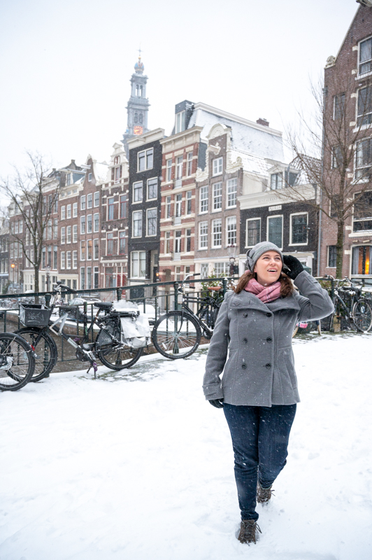 Jessica walking in the snow on an Amsterdam canal bridge
