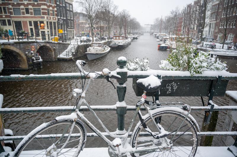 Bike covered in snow on Amsterdam bridge