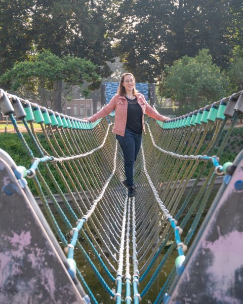 Jessica wearing a pink denim jack and black shirt with jeans on rope bridge