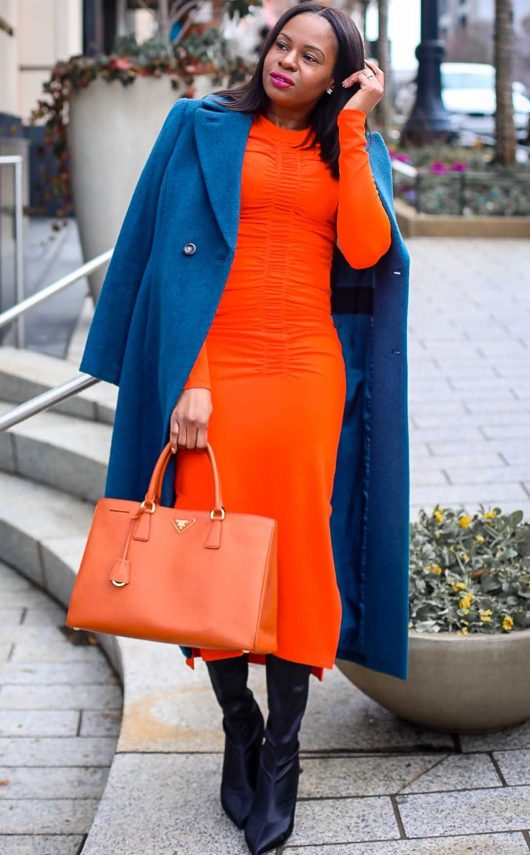 Atlanta Fashion blogger wearing an orange midi dress, orange Prada tote, black boots, and blue coat. Hair by Wella Hair USA -3