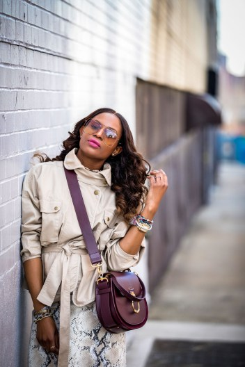 Atlanta lifestyle blogger Monica Awe-Etuk wearing a belted cargo jacket with a lafayette snakesin skirt and chloe snake boots. safari jacket belted jacket, utility trend, utility chic