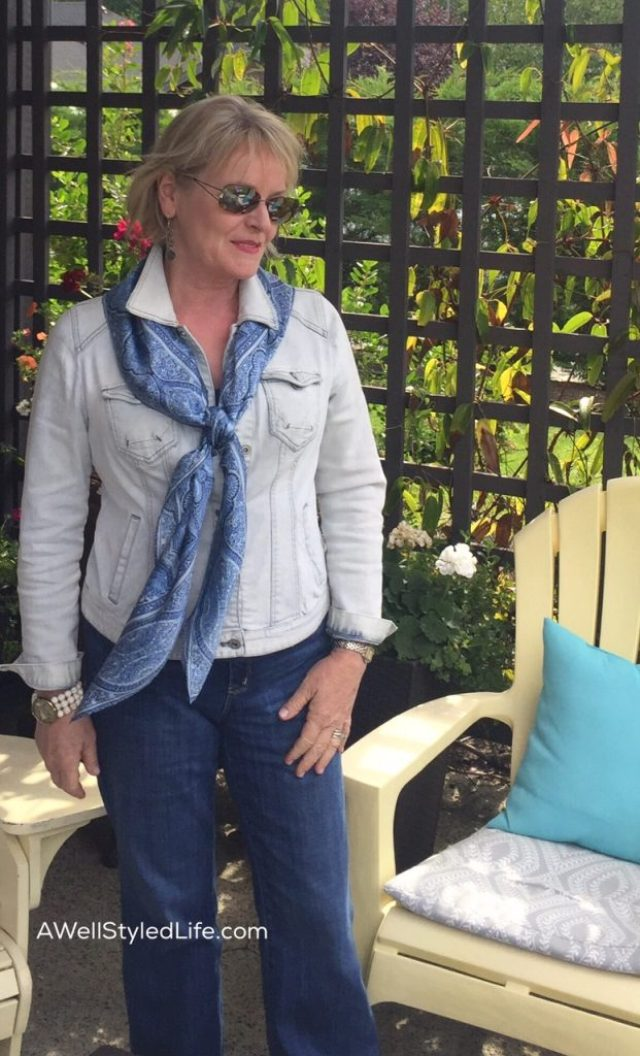 Pale washed denim jacket and deep blue jeans are pulled together by a scarf