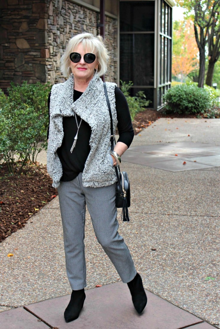 Jennifer Connolly of A Well Styled life wearing gray vest over black and white gingham, slacks