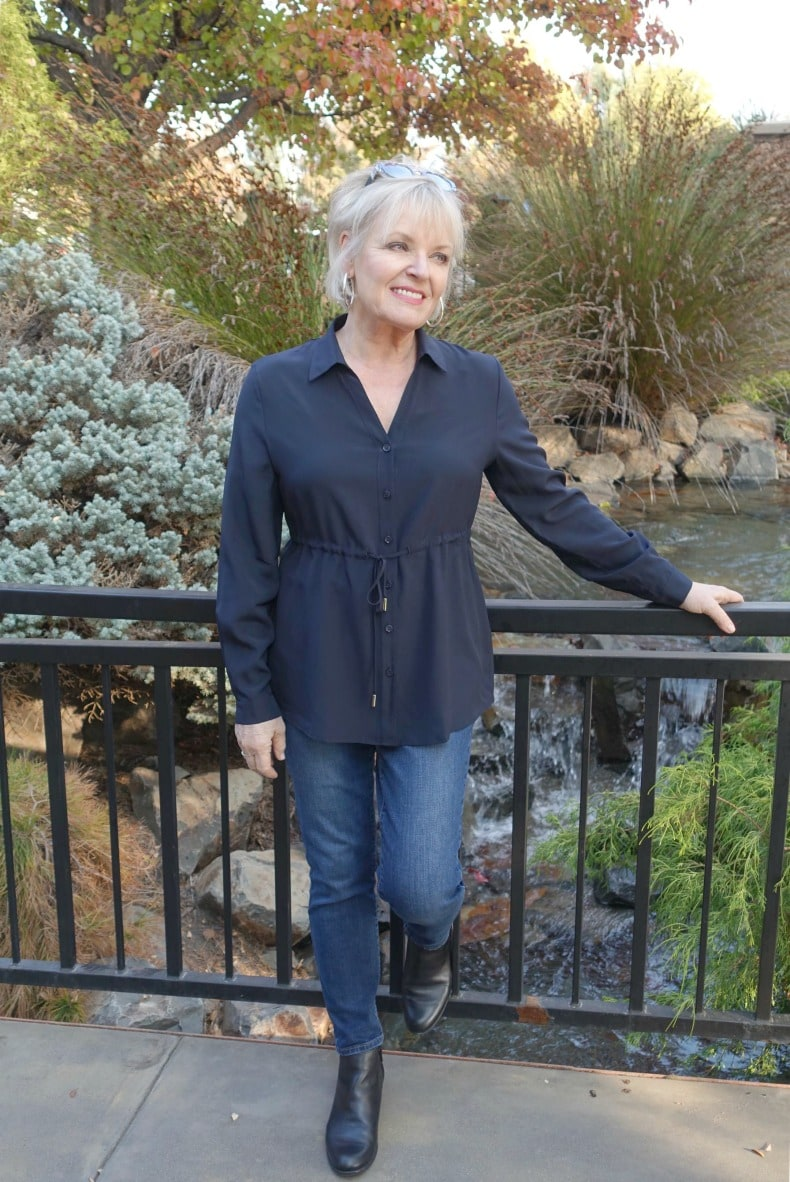 Jennifer Connolly wearing silk blouse with blue jeans and black booties