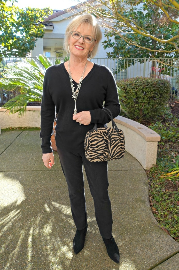 Jennifer Connolly of A Well Styled Life wearing black cashmere and jeans with animal print handbag