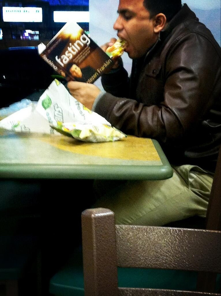 man-eating-while-reading-book-fasting-sad-people