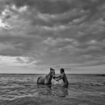 Only in Gili Trawangan at sunset. After a long day working, a time to unwind and give your horse a break-bath in this Indonesia paradise. (en Gili Trawangan Island,Lombok)